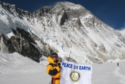 Kami Sherpa holds up Rotary banner, with Mt. Everest in the background